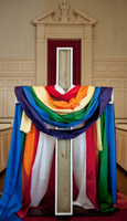 Cross draped with rainbow-colored fabric