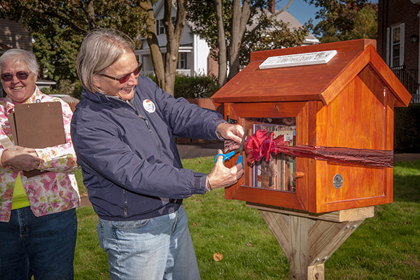 Pastor Shelly cuts the ribbon at the Little Free Library dedication.