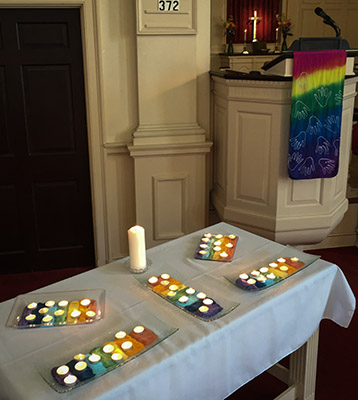 tea lights in beds of rainbow-colored salt as a rememberance for the Orlando dead